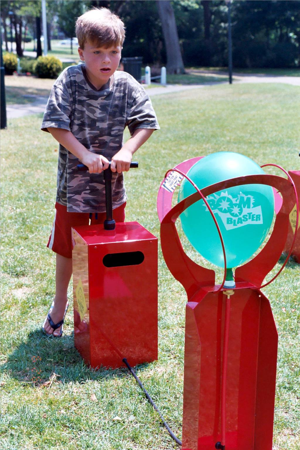 A young boy is trying his luck with Boom Blasters. Rent Boom Blasters from Bette's Party Rentals.